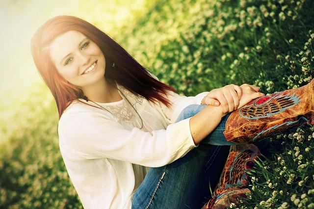 girl sitting in flowery grass